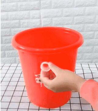 在垃圾桶的两侧上面1/3的位置,将两个饮料瓶盖用强力胶水对称黏上,并等待1小时左右风干